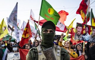 In the front row, a masked soldier stands holding his weapon against his chest. In the back, a row of Kurdish flags, banners and placards held by Kurdish protesters.