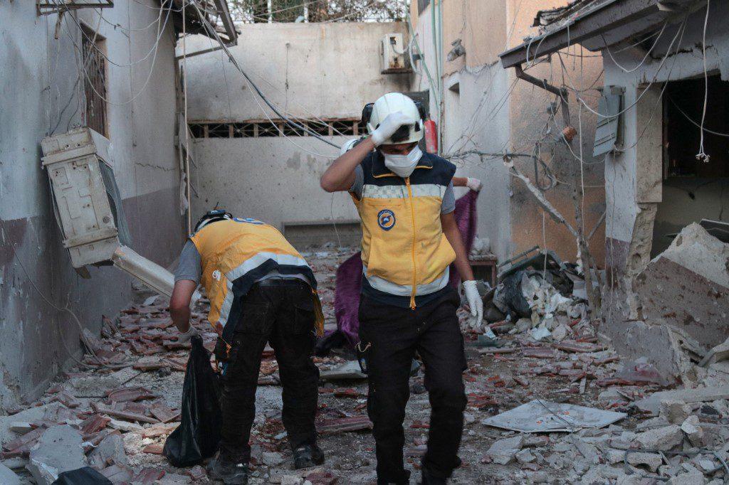 متطوعون في الدفاع المدني السوري (الخوذ البيضاء) يتفقدون أنقاضاً في مستشفى الشفاء بمدينة عفرين، بمحافظة حلب شمال سوريا، عقب استهدافه بقصف صاروخي، السبت الماضي، مصدره مواقع تسيطر عليها القوات الحكومية وقوات سوريا الديمقراطية (قسد) التي يهيمن عليها الكرد. وقد تسبب القصف بمقتل 15 مدنياً وإصابة قرابة 61 آخرين بعضهم حالته حرجة، بحسب بيان صادر عن الخوذ البيضاء، 12/ 6/ 2021 (أ ف ب).