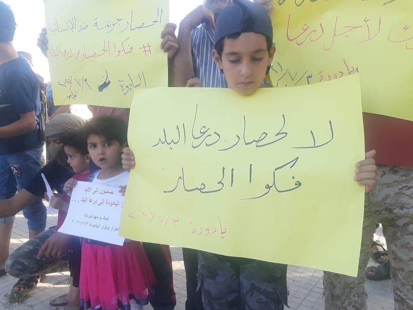 أطفال يشاركون في وقفة احتجاجية ببلدة اليادودة، غرب محافظة درعا، رفضاً للحصار المفروض على درعا البلد، 3/ 7/ 2021 (فيسبوك)