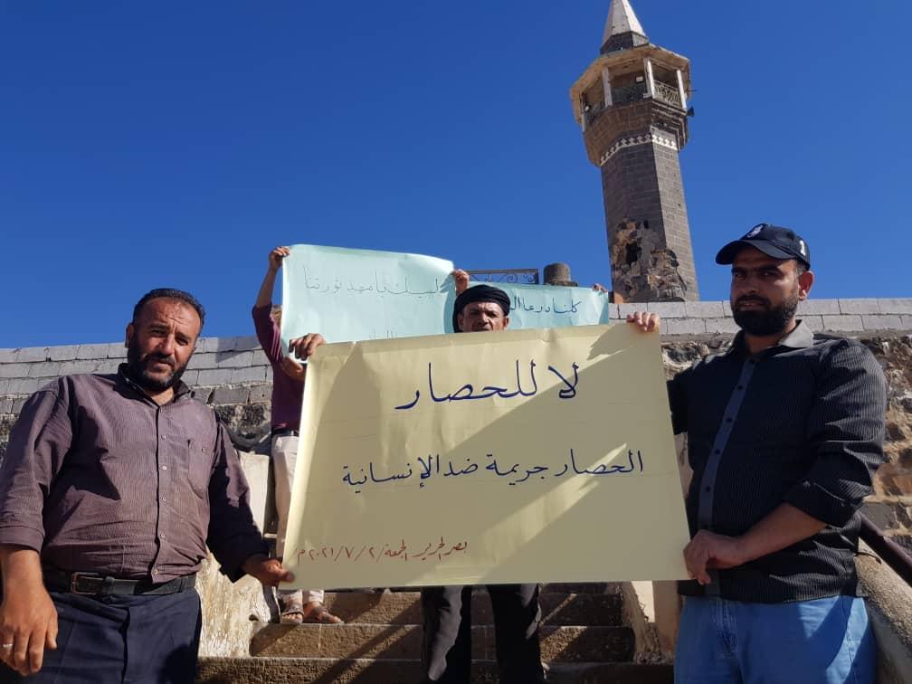 محتجون يرفعون لافتات في بلدة بصر الحرير شرق درعا تعبر عن رفض الحصار الذي تفرضه القوات الحكومية على درعا البلد، 2/ 7/ 2021 (تويتر)