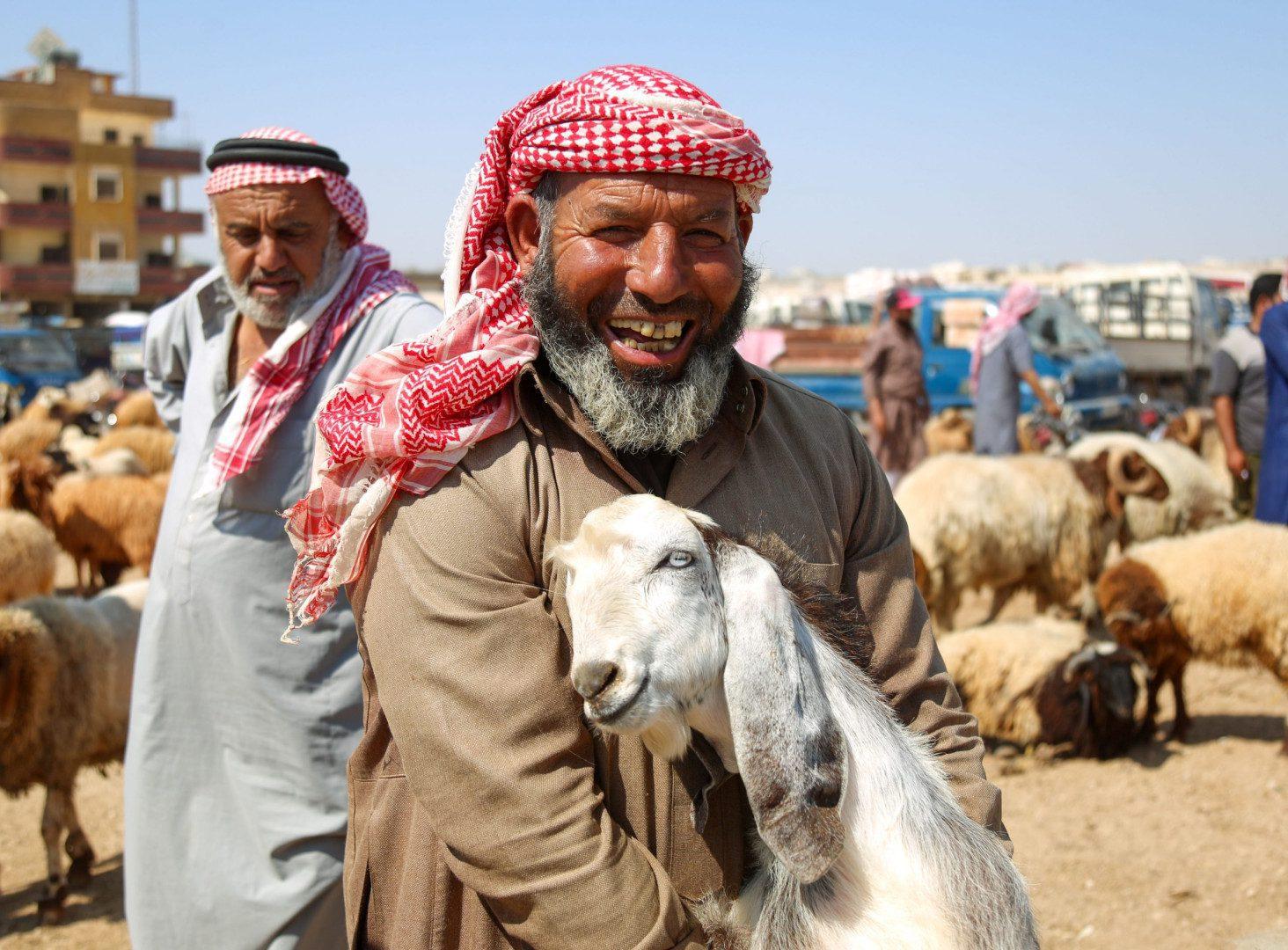رجل يحمل معزاة مبتسماً، في سوق الأغنام بمحافظة إدلب شمال غرب سوريا، عشية عيد الأضحى، في 17/ 7/ 2021