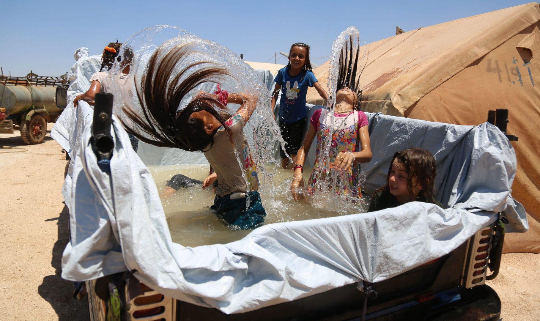 فتيات يلعبن بالمياه داخل صندوق سيارة بيك أب تم جعله أشبه بمسبح مصغر، لتمكين الأطفال من التعامل مع ارتفاع درجات الحرارة في مخيم خير الشام شمال بلدة كللي بمحافظة إدلب شمال غرب سوريا، في 12/ 7/ 2021.
