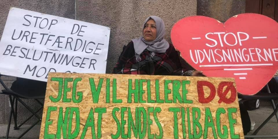 An elderly woman stands behind three large protest placards.