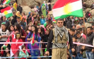 Barzan Hussein stands in front of a crowd, Kurdistan flags are visible in the background.