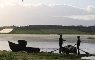 the silhouettes of two fishermen and their boat in front of a lake, in the light of dusk