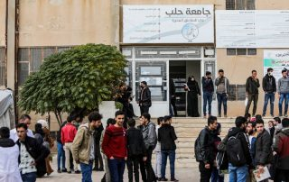 """Students stand in front of the door of the university. Above the door, a sign in Arabic: """"University of Aleppo"""""""