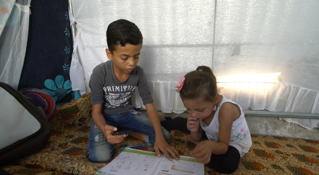 Abdulkarim al-Salloum helps his little sister with studying, using his father's mobile phone in the family's tent in the city of Salqin in Idlib province, 10/21/2020 (Violet - Syria Direct)