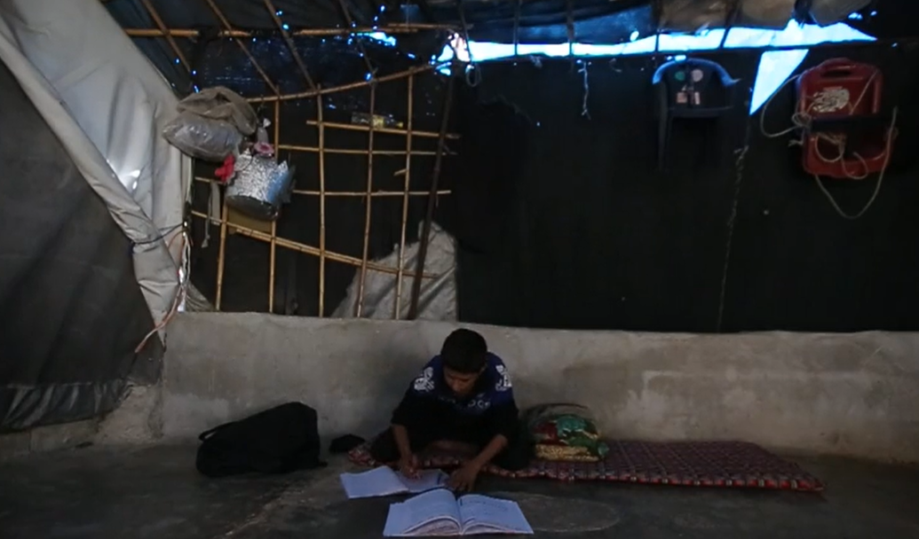 One of Mustafa al-Shahoud's children studies in the family's tent in the Aidoun camp in the city of Salqin in Idlib province, 10/21/2020 (Violet - Syria Direct)